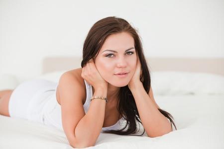 Posing dark-haired woman in her bedroom photo