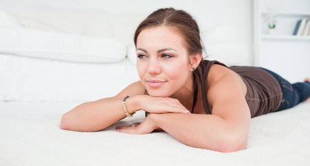 Young woman liying on a carpet in her living room photo