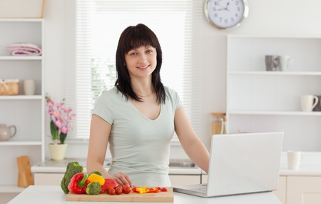 Lovely brunette woman relaxing with her laptop while standing in the kitchen photo