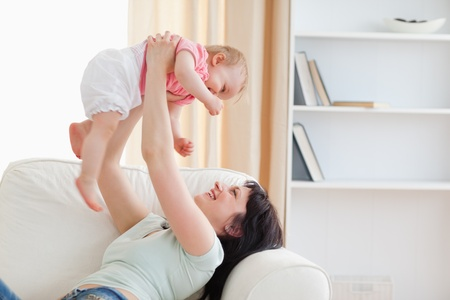 Charming woman holding her baby in her arms while sitting on a sofa in the living room photo