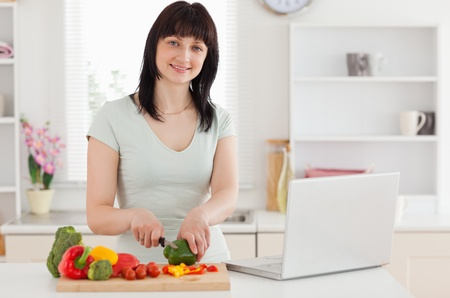 Smiling brunette woman cooking while relaxing with her laptop in the kitchen photo