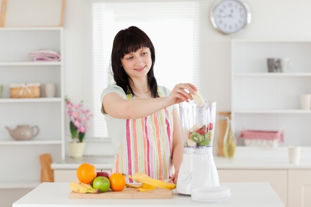 Gorgeous brunette woman putting vegetables in a mixer while standing in the kitchen photo