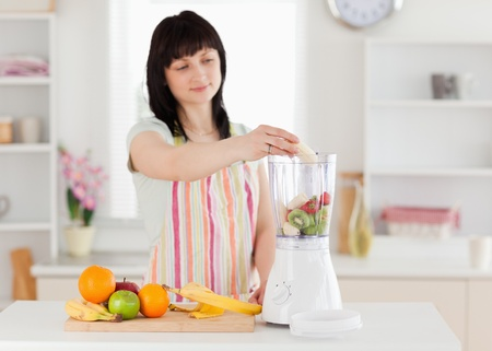 Lovely brunette woman putting vegetables in a mixer while standing in the kitchen photo
