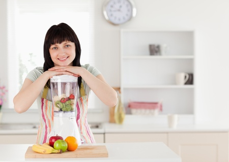 Attractive brunette woman posing with a mixer while standing in the kitchen photo