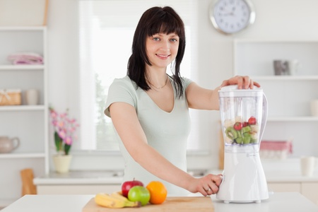 Charming brunette woman using a mixer while standing in the kitchen photo
