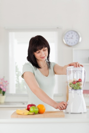 Cute brunette female using a mixer while standing in the kitchen photo