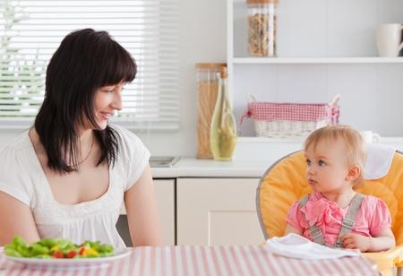 Hermosa mujer Morena, tener una comida con su bebé mientras estaba sentado en la cocina Foto de archivo - 10220907