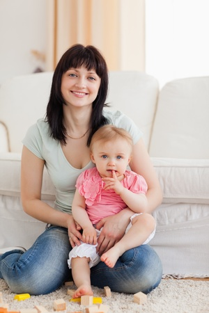 Beautiful woman holding her baby in her arms while sitting on a carpet in the living room Stock Photo - 10221241