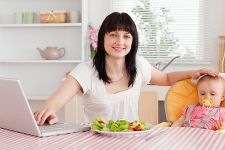 Attractive brunette woman eating a salad next to her baby while relaxing with her laptop in the kitchen photo