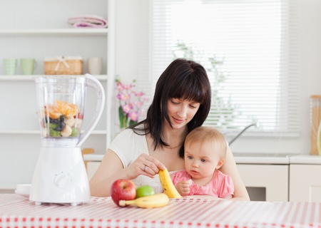 Cute brunette woman showing a banana to her baby while sitting in the kitchen photo