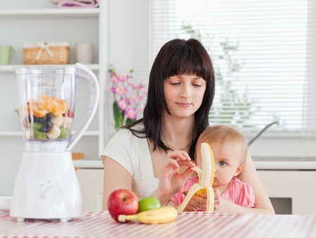 Cute brunette woman pealing a banana while holding her baby on her knees in the kitchen photo