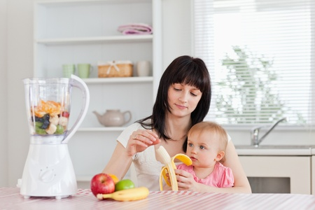 pealing: Attractive brunette woman pealing a banana while holding her baby on her knees in the kitchen