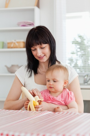Beautiful brunette woman pealing a banana while holding her baby on her knees in the kitchen photo