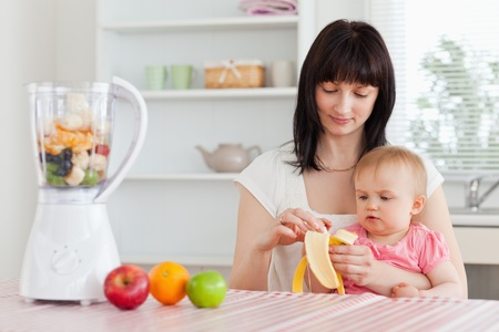 pealing: Gorgeous brunette woman pealing a banana while holding her baby on her knees in the kitchen Stock Photo