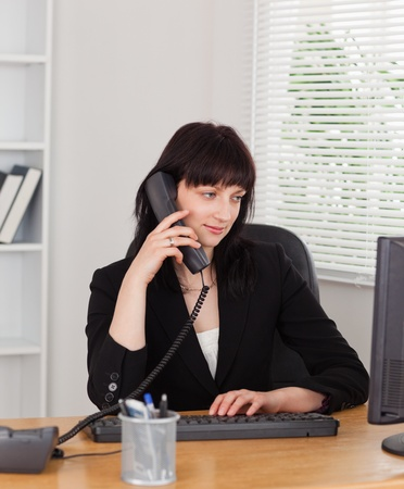 Beautiful brunette woman on the phone while working on a computer in the office photo