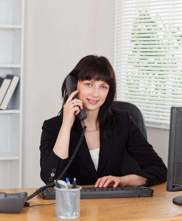Good looking brunette woman on the phone while working on a computer in the office photo