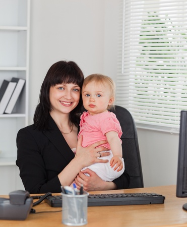 Attractive brunette woman posing while holding her baby on her knees in the office photo