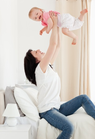 Beautiful brunette woman playing with her baby while sitting on a bed in her appartment Stock Photo - 10221184