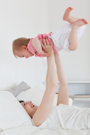 Pretty brunette woman playing with her baby while lying on a bed in her appartment photo