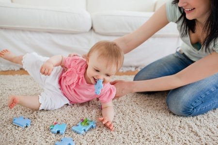 Lovely woman and her baby playing with puzzle pieces while sitting on a carpet in the living room photo