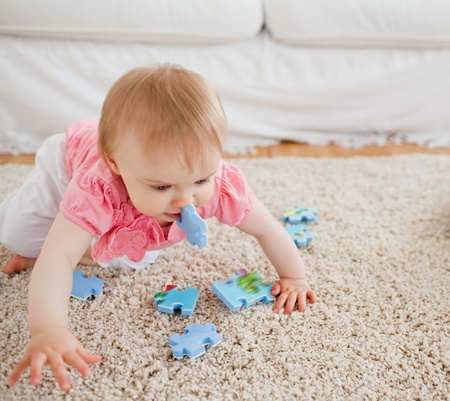 Lovely blond baby playing with puzzle pieces on a carpet in the living room photo