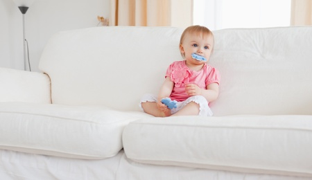 Lovely blond baby playing with puzzle pieces while sitting on a sofa in the living room photo