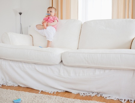 Lovely blond baby playing with puzzle pieces while standing on a sofa in the living room photo