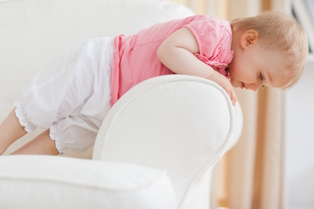 Cute blond baby standing on a sofa in the living room photo