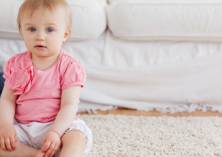 Lovely blond baby looking at the camera while sitting on a carpet in the living room photo