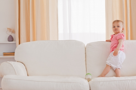 Baby standing on a sofa in the living room Stock Photo - 10221101