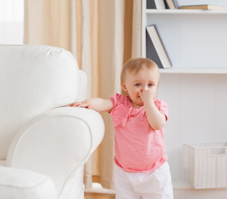 family on couch: Baby standing near a sofa in the living room