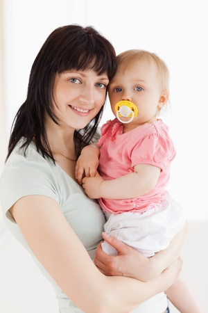 Good looking woman holding her baby in her arms while standing in the living room photo