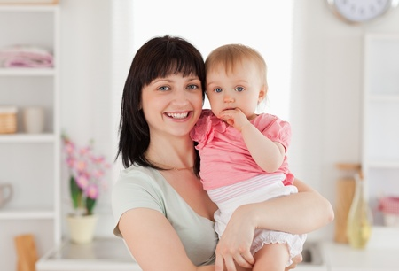 Beautiful woman holding her baby in her arms while standing in the kitchen photo