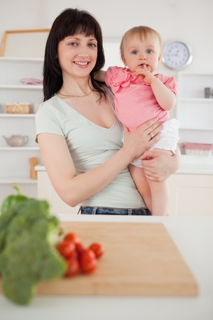 Pretty woman holding her baby in her arms while standing in the kitchen photo