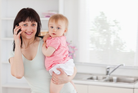 Beautiful woman on the phone while holding her baby in her arms in the kitchen photo