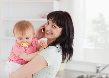 Good looking woman on the phone while holding her baby in her arms in the kitchen photo