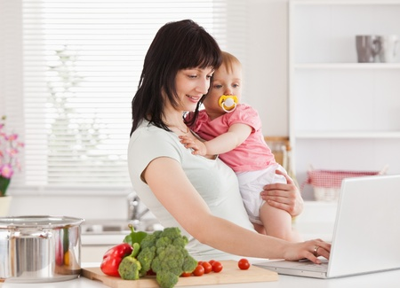 Good looking woman holding her baby in her arms while standing in the kitchen photo