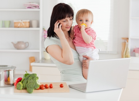 Good looking brunette woman on the phone while holding her baby in her arms in the kitchen Stock Photo - 10220947
