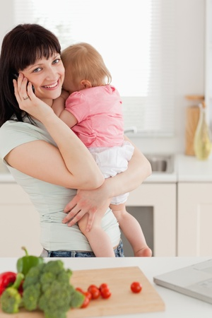 Cute brunette woman on the phone while holding her baby in her arms in the kitchen photo