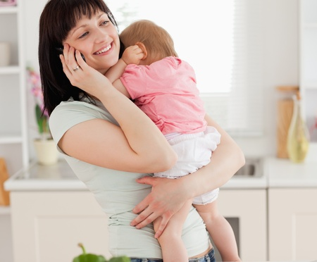 Lovely brunette woman on the phone while holding her baby in her arms in the kitchen photo