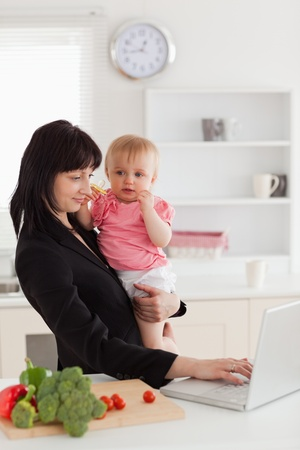 Attractive brunette woman in suit holding her baby in her arms while working with her laptop in the kitchen photo