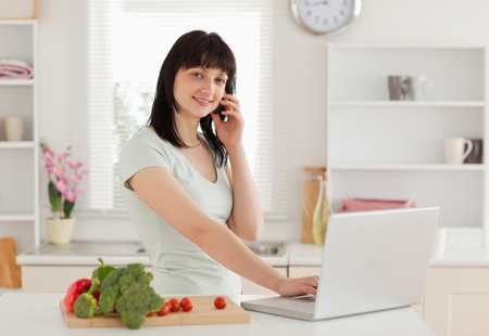 Pretty brunette woman on the phone while relaxing with her laptop in the kitchen photo