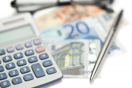 Pengar, penna, glasögon och vinklade miniräknare på en vit bakgrund