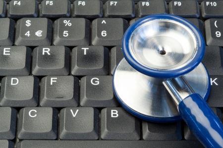 Blue stethoscope on keyboard photo