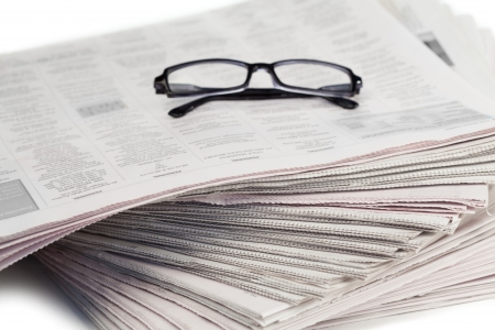 pile reuse: Newspapers and black glasses on a white a background