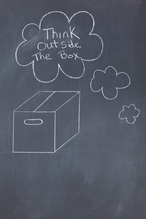 Close up of a blackboard with a closed box and think outside the box drawn on it   photo