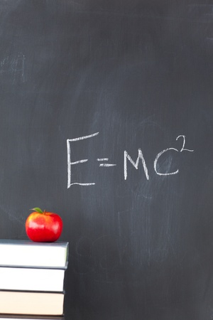 Stack of books with a red apple and a blackboard with a formula written on it photo