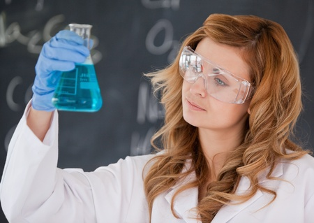 Beautiful female scientist looking at a flask in a laboratory Stock Photo - 10232281