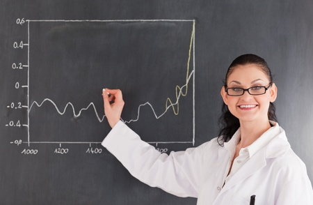 normal distribution: Smiling scientist drawing charts on the blackboard and looking at the camera