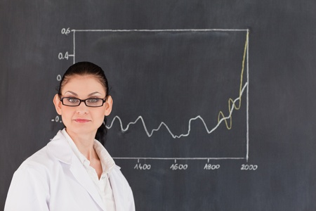 Isolated scientist standing near the blackboard and looking at the camera photo